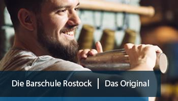 Eine Werbeanzeige für die Barschule in Rostock. Auf ihr ist ein lächelnder Mann zu sehen, der fröhlich einen Cocktail-Shaker schüttelt.